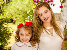 Smiling beautiful mom hugging her pretty daugher in beige dress wearing two red ties in hair.  Royalty Free Stock Photos
