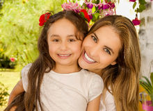Smiling beautiful mom hugging her pretty daugher in beige dress wearing two red ties in hair.  Stock Photography