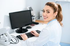 smiling beautiful ophthalmologist working with computer royalty free stock photography