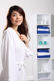Smiling beautiful oriental woman wearing bath robe Stock Photos