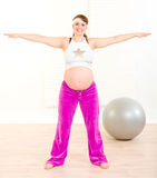Smiling beautiful pregnant female doing exercise Royalty Free Stock Images