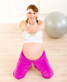 Smiling beautiful pregnant female doing fitness Royalty Free Stock Image
