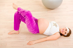 Smiling beautiful pregnant female doing fitness Stock Photos