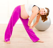 Smiling beautiful pregnant woman doing exercise Royalty Free Stock Image