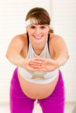 Smiling beautiful pregnant woman doing exercise Royalty Free Stock Photos