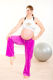 Smiling beautiful pregnant woman doing exercise Royalty Free Stock Images