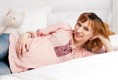 The smiling beautiful pregnant woman lies on a bed Stock Image