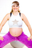 Smiling beautiful pregnant woman making gymnastics Royalty Free Stock Photo