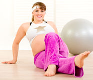 Smiling beautiful pregnant woman making gymnastics Stock Photography