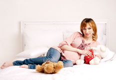 The smiling beautiful pregnant woman sits on a bed Royalty Free Stock Images