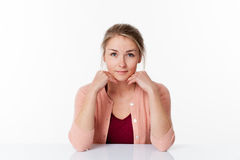 Smiling beautiful 20s blond woman sitting at sparse desk Royalty Free Stock Photography