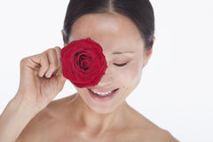 Smiling, beautiful, shirtless woman holding a red rose to her eye, studio shot Stock Photos