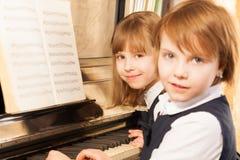 Smiling beautiful small girls playing piano Stock Photography