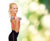 Smiling beautiful sporty woman with dumbbell Stock Photos
