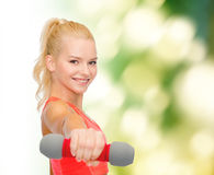 Smiling beautiful sporty woman with dumbbell Royalty Free Stock Image