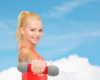 Smiling beautiful sporty woman with dumbbell Royalty Free Stock Photos