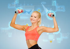 Smiling beautiful sporty woman with dumbbells Stock Photo
