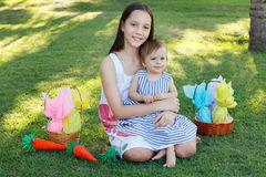 Smiling beautiful teen girl holding sister baby with chocolate e Royalty Free Stock Photos
