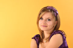 Smiling Beautiful Teenage Girl. In purple dress, on a yellow background with copy space Stock Image