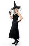 Smiling beautiful witch. Smiling witch standing on white background Stock Images