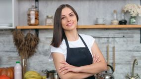 Smiling beautiful woman in apron posing with crossed hand at cosiness kitchen interior. Medium close-up. Portrait of adorable pleasant housewife having positive stock video footage
