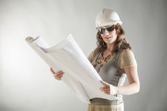 Smiling beautiful woman architect. With documents wearing sunglasses and helmet Royalty Free Stock Photos