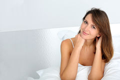 Smiling and beautiful woman in bed Stock Images