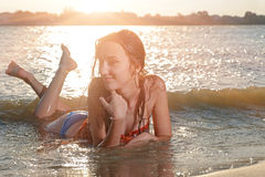 Smiling beautiful woman in bikini lying on a beach Stock Image