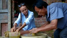 Woman in blue blouse learns to make clay pot on wheel. Smiling beautiful woman in blue blouse learns to make clay pot on rotating potter wheel with master stock video footage