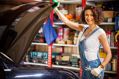 Smiling beautiful woman car mechanic. In blue overalls lifted the hood of the car and looks at the camera. scene in the garage Royalty Free Stock Image