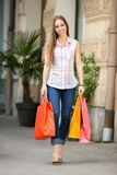 Beautiful woman carrying some shopping bags. Smiling beautiful woman carrying some shopping bags royalty free stock photos