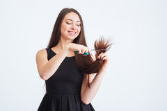 Smiling beautiful woman cutting splitting ends of hair with scissors Stock Image