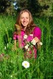 Smiling beautiful woman among the daisies Stock Photos