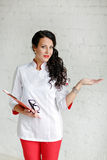 Smiling beautiful woman doctor in a white-and-red uniforms with Royalty Free Stock Photo