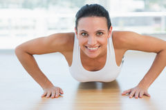 Smiling beautiful woman doing push ups in gym Stock Photo