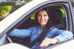 Smiling woman driving her car. Toned image stock image