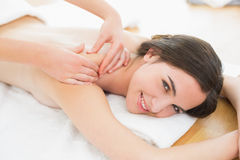 Smiling beautiful woman enjoying shoulder massage at beauty spa Stock Images