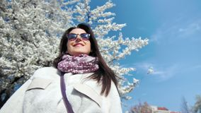Smiling beautiful woman enjoying sunshine at spring garden with white flowering sakura tree and blue sky. Low angle. Medium close-up adorable happy girl playing stock video footage