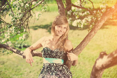 Smiling beautiful woman and flowering tree Royalty Free Stock Photography
