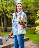 Smiling beautiful woman gardener with flowers Stock Images