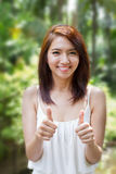 Smiling beautiful woman giving two thumbs up Stock Photo