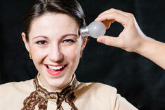 Smiling beautiful woman having an idea with light bulb over her head on black Royalty Free Stock Images