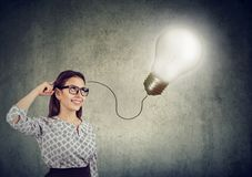 Smiling beautiful woman having an idea with light bulb over her head stock images