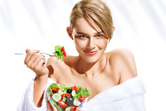 Smiling beautiful woman with healthy vegetable salad. Photo of blonde woman in bathrobe isolated on white background. Diet. Healthy lifestyle Stock Photos