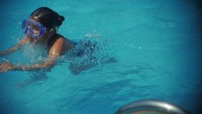 Smiling beautiful woman and her cute child in the pool. Portrait of a happy family relax - having fun together. stock footage