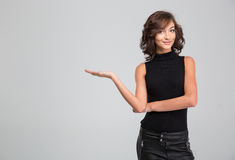 Smiling beautiful woman hoding copyspace on the palm over background. Smiling young curly attractive beautiful woman hoding copyspace on the palm over white royalty free stock image