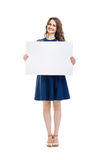 Smiling beautiful woman holding empty sign board. Isolated on white background. Full length portrait Stock Photo