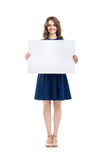 Smiling beautiful woman holding empty sign board. Isolated on white background. Full length portrait Royalty Free Stock Photography