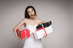 Smiling beautiful woman holding gifts. Young surprised woman holding multiple gifts. Beautiful elegant brunette carrying her presents Royalty Free Stock Photos