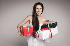 Smiling beautiful woman holding gifts. Young surprised woman holding multiple gifts. Beautiful elegant brunette carrying her presents Royalty Free Stock Image
